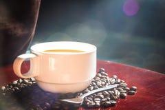 taza de café y backgrouds del bokeh de las habas Foto de archivo libre de regalías