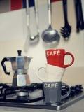 Taza de café y cafetera apiladas del vintage en estufa de cocina Imágenes de archivo libres de regalías