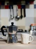 Taza de café y cafetera rojas del vintage en estufa de cocina Foto de archivo libre de regalías