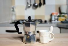 Taza de café y cafetera rojas del vintage en estufa de cocina Imágenes de archivo libres de regalías