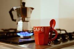 Taza de café y cafetera rojas en estufa de cocina Imagenes de archivo