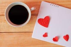 Taza de café y de corazones en un fondo de madera Café en calendario día de San Valentín con concepto del café Fotografía de archivo libre de regalías