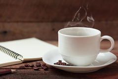 Taza de café y cuaderno Foto de archivo