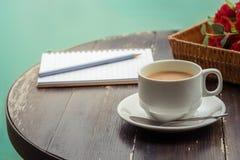 Taza de café y de cuaderno abierto en la tabla de madera Fotos de archivo