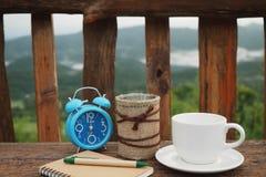 Taza de café y cuaderno en la tabla Foto de archivo libre de regalías