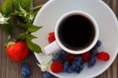 Taza de café y de bayas frescas en una tabla de madera Imagen de archivo libre de regalías
