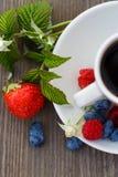 Taza de café y de bayas frescas en una tabla de madera Fotografía de archivo