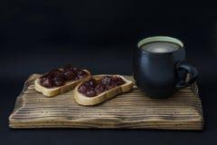 Taza de café y de bocadillo con el atasco Foto de archivo libre de regalías