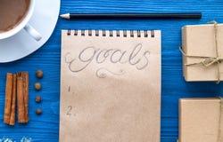 Taza de café y de cuaderno con las metas por Año Nuevo Imágenes de archivo libres de regalías