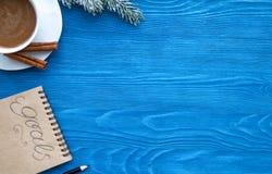 Taza de café y de cuaderno con las metas por Año Nuevo Foto de archivo libre de regalías