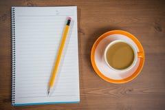 Taza de café y de cuaderno en de madera foto de archivo libre de regalías