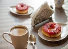 Taza de café y de donaughts en la tabla Imágenes de archivo libres de regalías
