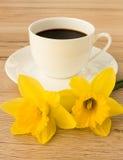 Taza de café y de dos narcisos Imágenes de archivo libres de regalías
