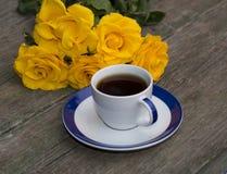 Taza de café y de flores amarillas en una tabla vieja Foto de archivo