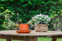 Taza de café y de flores con el árbol en fondo Foto de archivo libre de regalías