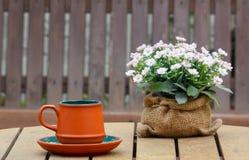 Taza de café y de flores con el asiento de madera en fondo Foto de archivo libre de regalías