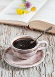 Taza de café y de flores en el libro abierto fotografía de archivo