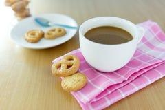 Taza de café y de galletas en la tabla de madera Fotografía de archivo
