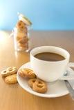Taza de café y de galletas en la tabla de madera Foto de archivo