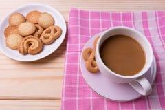 Taza de café y de galletas en piso de madera Imágenes de archivo libres de regalías