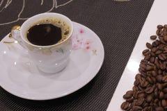 Taza de café y de granos de café Foto de archivo