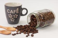 Taza de café y de granos de café derramados del tarro de cristal fotografía de archivo