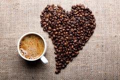 Taza de café y de granos de café en la forma del corazón Fotos de archivo