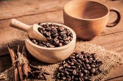 Taza de café y de granos de café en la tabla de madera Imagen de archivo