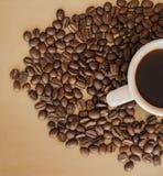 Taza de café y de granos en un fondo del oro Fotografía de archivo libre de regalías