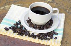 Taza de café y de habas en fondo de madera Imagen de archivo