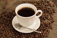 Taza de café y de habas marrones alrededor Fotografía de archivo libre de regalías