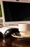 Taza de café y de libro al lado del ordenador Foto de archivo