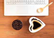 Taza de café y de ordenador portátil en la tabla de madera foto de archivo libre de regalías