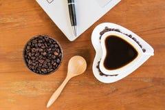 Taza de café y de ordenador portátil en la tabla de madera imagen de archivo