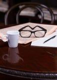 Taza de café y de periódico fotos de archivo
