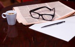Taza de café y de periódico foto de archivo
