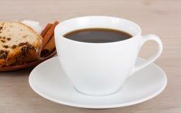Taza de café y de queque de frutas en un platillo. Fotografía de archivo