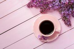 Taza de café y de ramas de la lila floreciente en la tabla de madera rosada Fotografía de archivo