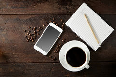 taza de café y de smartphone en la madera Fotos de archivo libres de regalías