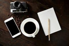 taza de café y de smartphone en la madera Foto de archivo