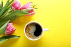 Taza de café y de tulipanes rosados en el fondo amarillo, visión superior Fotos de archivo
