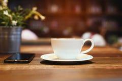 Taza de café y de un teléfono en el escritorio Foto de archivo libre de regalías