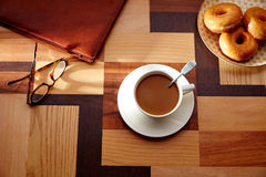 Taza de café y dona con los vidrios en la tabla retra Imagen de archivo libre de regalías