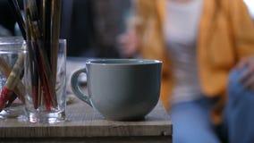 Taza de café y equipo artístico en la tabla de trabajo almacen de metraje de vídeo