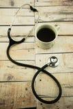 Taza de café y estetoscopio en fondo de madera Imagenes de archivo