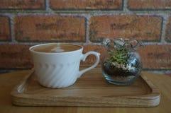 Taza de café y florero de flores en café Imagen de archivo