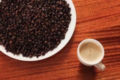 Taza de café y de granos de café asados Imágenes de archivo libres de regalías