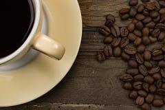 Taza de café y granos de café asados en fondo de madera Fotografía de archivo libre de regalías