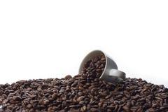 Taza de café y granos de café derramados Imagen de archivo libre de regalías