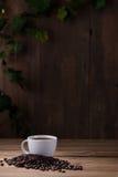 Taza de café y granos de café en de madera Imagen de archivo